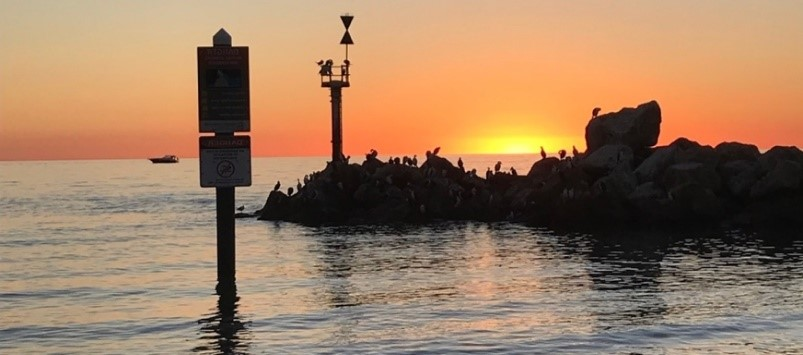 A breakwater is on the right of the image. The sun is setting behind the breakwater, and reflecting off the water.